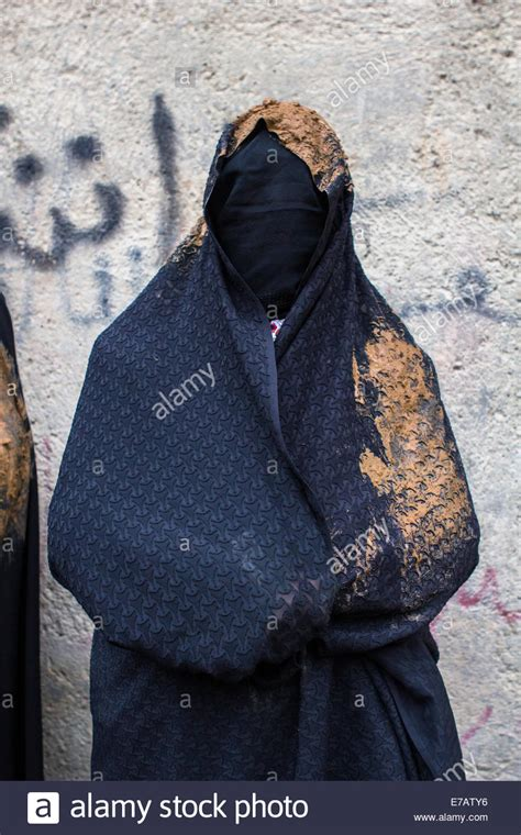 A Shiite Muslim woman, wearing a black chador covered with